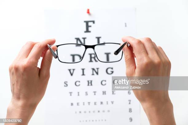 modern fashion glasses in the hands of a woman or girl, next to the diagram of the snellen vision test. ophthalmology, visual acuity testing, treatment and prevention of eye diseases. the concept of poor vision, blindness, treatment of an ophthalmologist. - scrutiny stock pictures, royalty-free photos & images