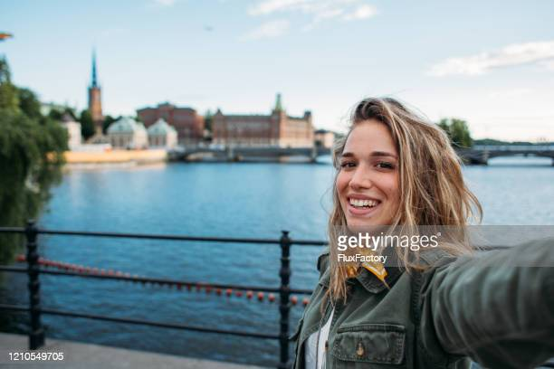 modern fashionable woman taking photo of hersefl in front of gamla stan - one young woman only stock pictures, royalty-free photos & images