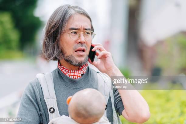 電話で話しながら、彼の赤ちゃんを運ぶ現代の父 - シングルファザー ストックフォトと画像