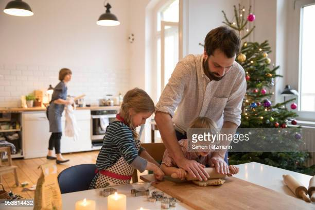 Modern father making cookies with daughter and son at christmas