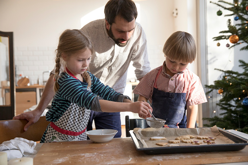 Modern father making cookies with daughter and son at christmas - gettyimageskorea