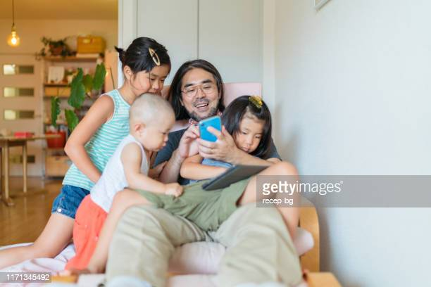 modern father taking care of his children at home - baby human age stock pictures, royalty-free photos & images