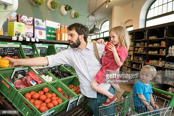 Modern father with two kids shopping organic food