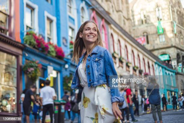 modern female tourist spending excited day visiting victoria street in edinburgh - floral pattern dress stock pictures, royalty-free photos & images