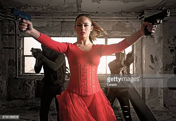 modern female warrior wearing elegant red dress in urban setting - corset stock pictures, royalty-free photos & images