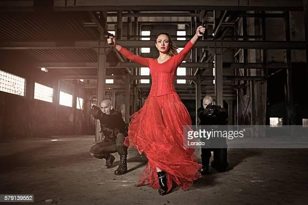 Modern female warrior wearing elegant red dress in urban setting