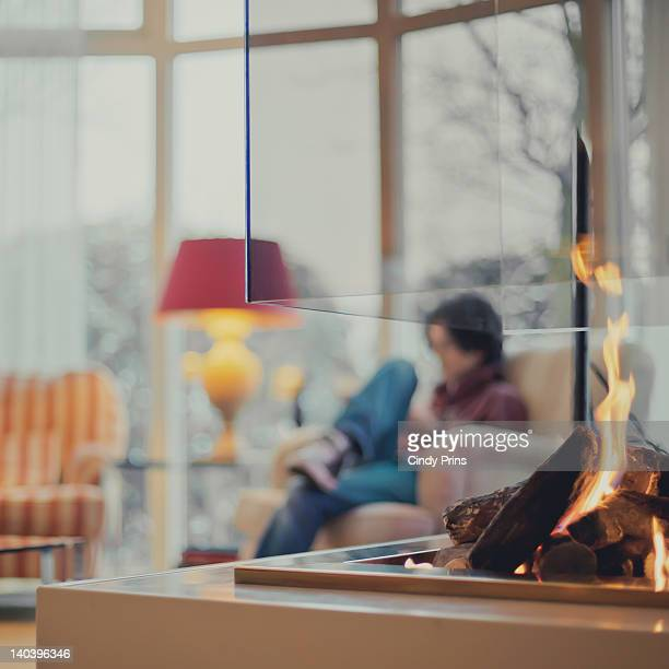 Modern fireplace with boy sitting in chair