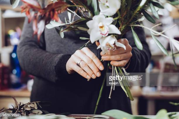 modern florist working with flowers in workshop - with detail on hands - composizione di fiori foto e immagini stock