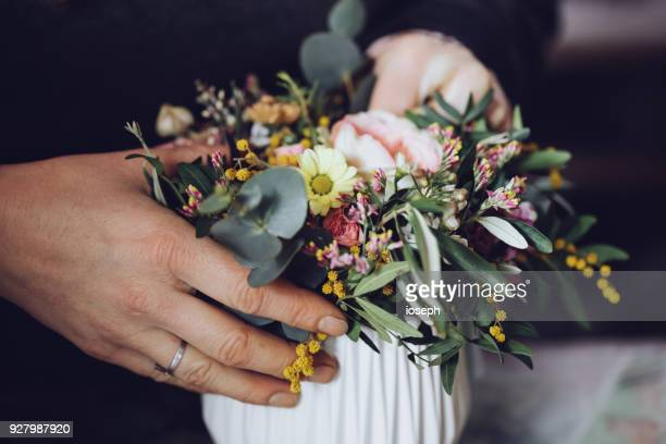 Modern florist working with flowers in workshop - with detail on hands