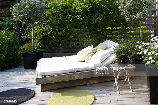 Modern garden with an outdoor bed in the afternoon sun
