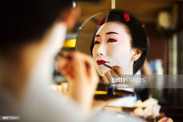 a modern geisha or maiko woman being prepared in traditional fashion, with white face makeup. - geisha photos et images de collection