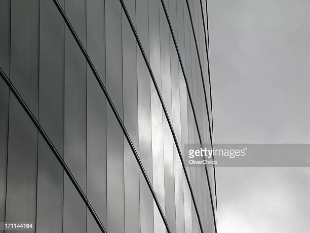 Architecture moderne à la façade de verre, qui reflètent les nuages.