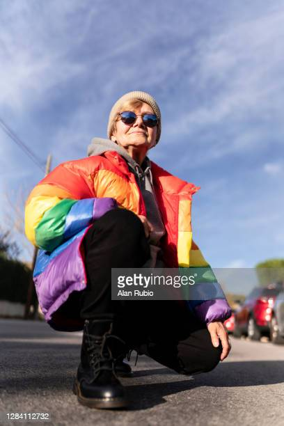 modern grandmother in rainbow coat posing in the middle of the street. - vintage lesbian photos stock pictures, royalty-free photos & images
