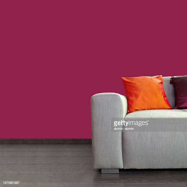 Modern gray sofa and colorful pillows against purple wall
