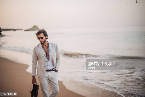 modern guy taking a walk on the beach - modella foto e immagini stock
