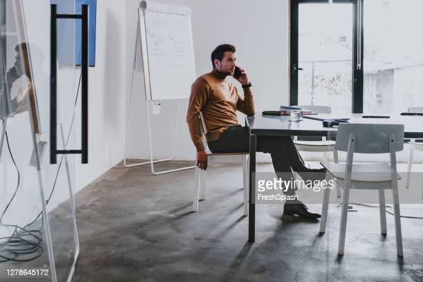 一人で会議室に座って、彼のスマートフォンで電話をかける現代のハンサムなビジネスマン - 様式 ストックフォトと画像