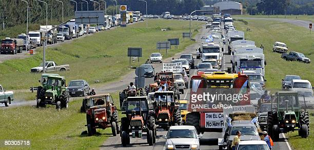 A modern harvester leads a caravan about four miles long of tractors and trucks loaded with angry farmers on strike against increased taxes that...