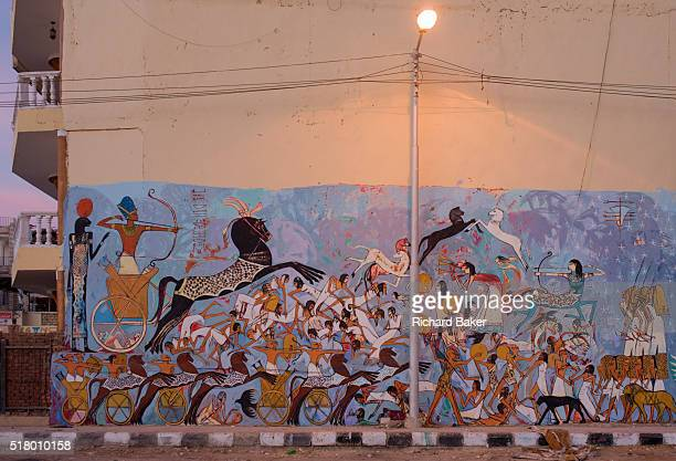 Modern hieroglyphic artwork painted on a wall of local wasteground in the village of Gezirat on the West Bank of Luxor Nile Valley Egypt The pictures...