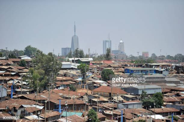Modern highrise office blocks break the skyline above the sprawling Kibera slum in the foreground in the Kenyan capital, Nairobi, on January 16,...