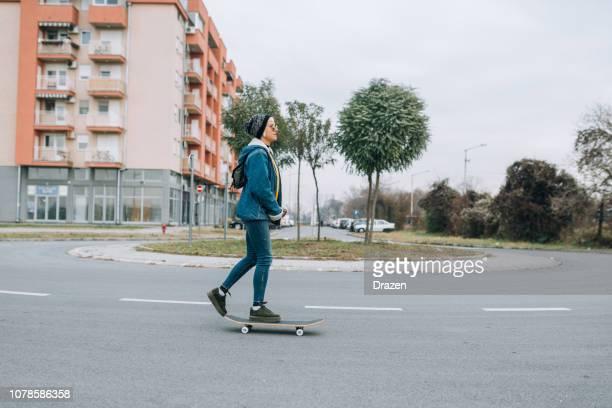 Femme de hipster moderne bénéficiant d'une journée tranquille sans aucun trafic ne les rues, planche à roulettes