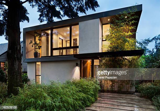modern home exterior lit at twilight - moderno foto e immagini stock