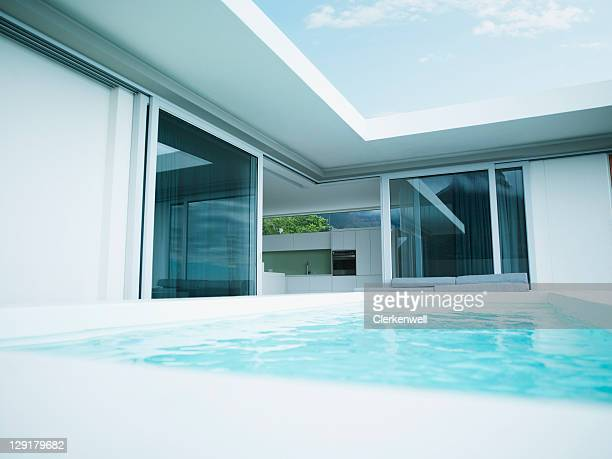 modern house and swimming pool - patio doors stock pictures, royalty-free photos & images