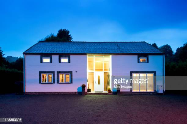 modern house illuminated at twilight - zonsopgangen en zonsondergangen stockfoto's en -beelden