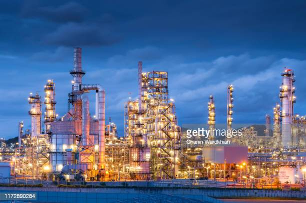 a modern, illuminated refinery is visible at dusk. lights from the buildings and streets glow. - gas refinery stock photos and pictures