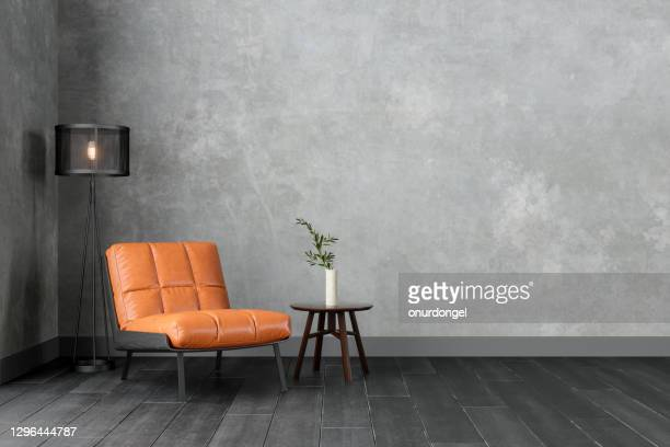 modern interior with orange colored leather armchair, sconce, coffee table and gray wall. - living room stock pictures, royalty-free photos & images