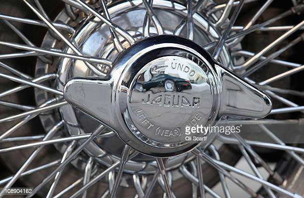 Modern Jaguar car is reflected in the wheel hub of a Jaguar E-type car on the 50th anniversary of the E-type outside London's Design Museum on...