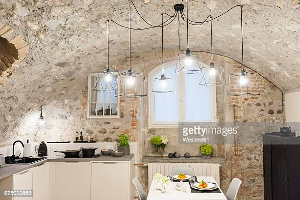 Modern kitchen in old stone house with freshly cooked pasta on table