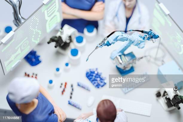 laboratorio moderno con bracci robotici - scienziata foto e immagini stock