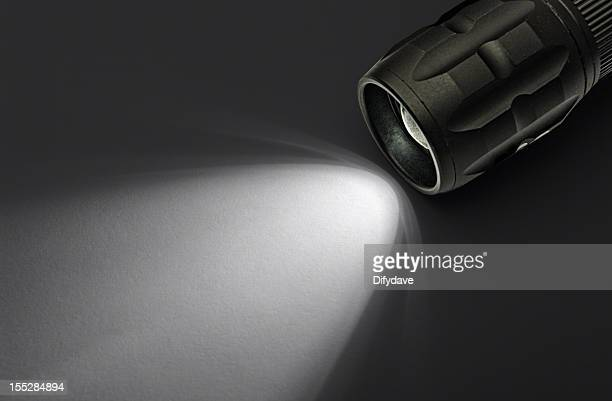 Modern LED Torch With Beam On White Paper Background