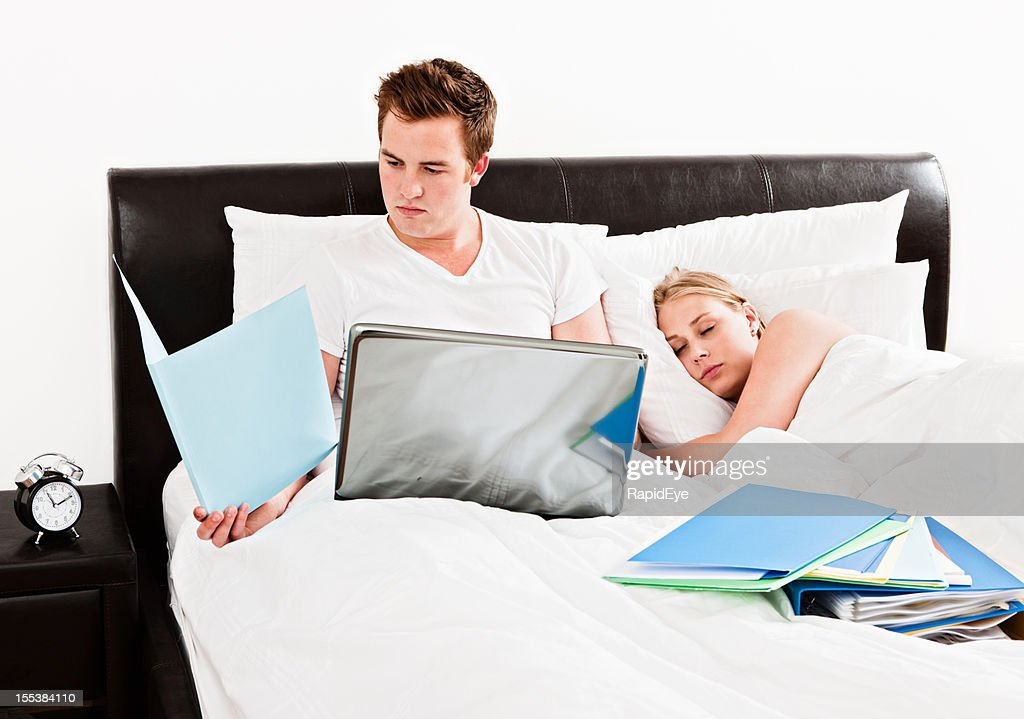 Modern life: man working in bed as partner sleeps : Stock Photo