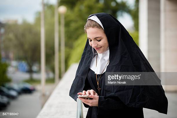modern life - nun with mobile - nun stock pictures, royalty-free photos & images