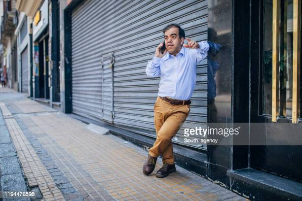 modern little gentleman talking on mobile on the street - dwarf man stock pictures, royalty-free photos & images