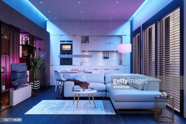 modern living room and open plan kitchen at night with neon lights. - ambient light stock pictures, royalty-free photos & images