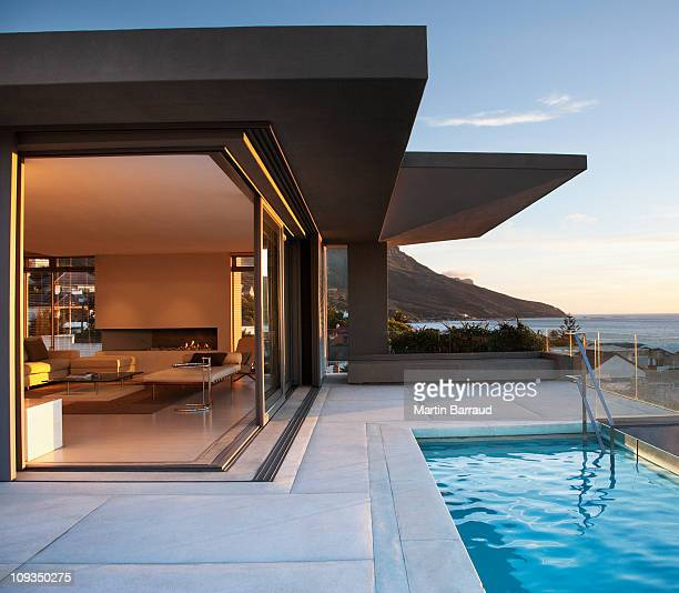 modern living room and patio next to swimming pool - luxury stock pictures, royalty-free photos & images