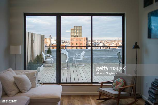 Modern living room and patio on urban rooftop, New York, New York, United States