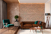 Modern living room interior with brick wall blank wall, leather brown sofa, green lounge chair, table, wooden wall and floor, plants, carpet, hidden lighting. 3d render illustration mockup.