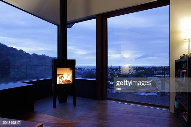 Modern living room with fireplace at dusk