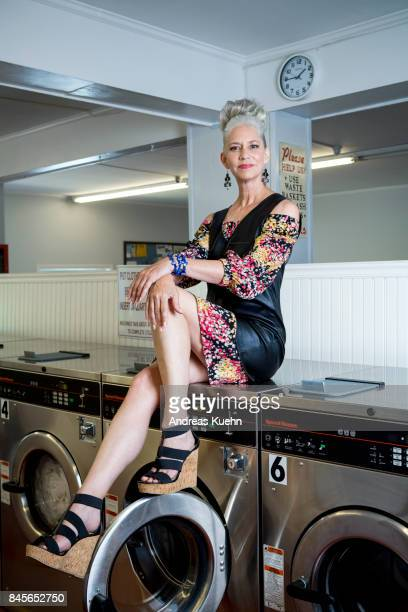 Modern looking woman with high heels in her late fifties with long, silvery, grey hair in an up do sitting on top of a washing machine inside a laudromat.