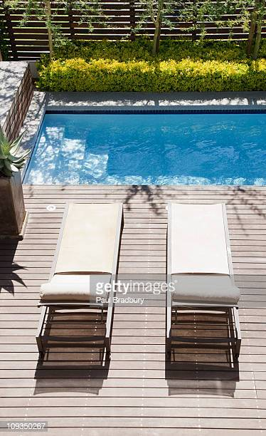 Modern lounge chairs next to swimming pool