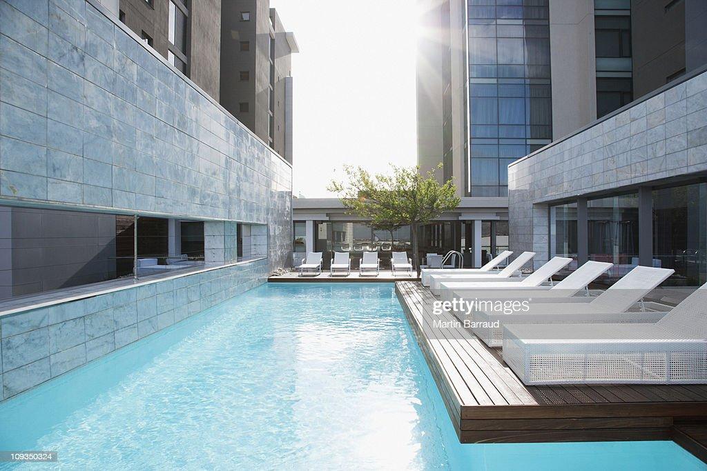 Modern lounge chairs next to swimming pool : Stock Photo