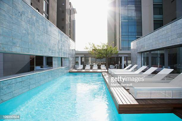 modern lounge chairs next to swimming pool - hotel stock pictures, royalty-free photos & images