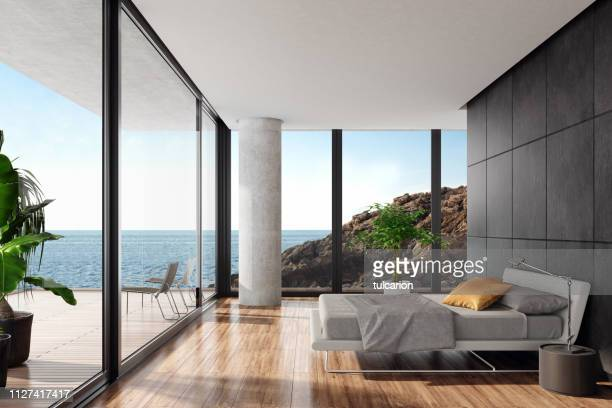 modern luxurious bedroom in a seaside villa with black stone wall - hotel stock pictures, royalty-free photos & images