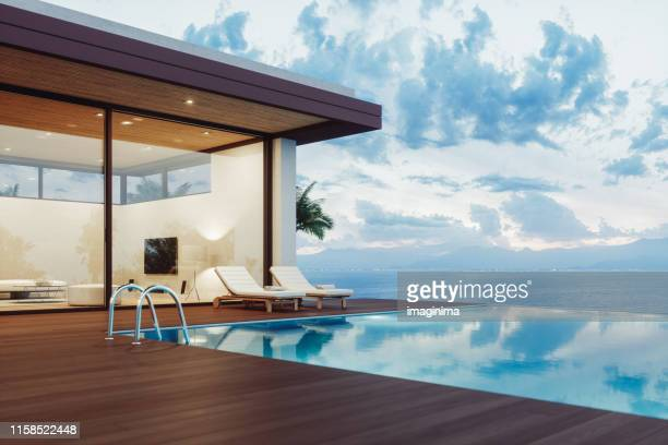 modern luxury house with infinity pool at dawn - luxury stock pictures, royalty-free photos & images