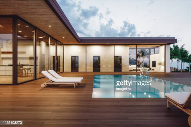 modern luxury house with private swimming pool at dusk - moderno foto e immagini stock