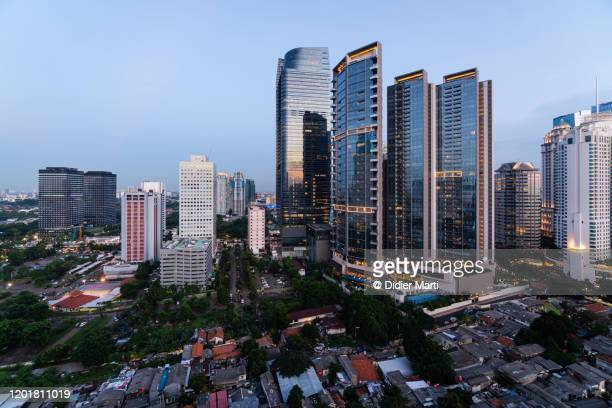 modern luxury office and condominium towers contrasts with run down poor residential district in jakarta - desequilibrio fotografías e imágenes de stock