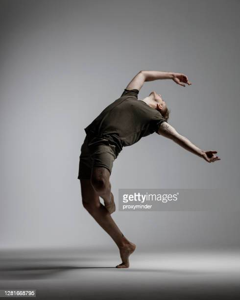 modern male dancer on gray background - dancer stock pictures, royalty-free photos & images